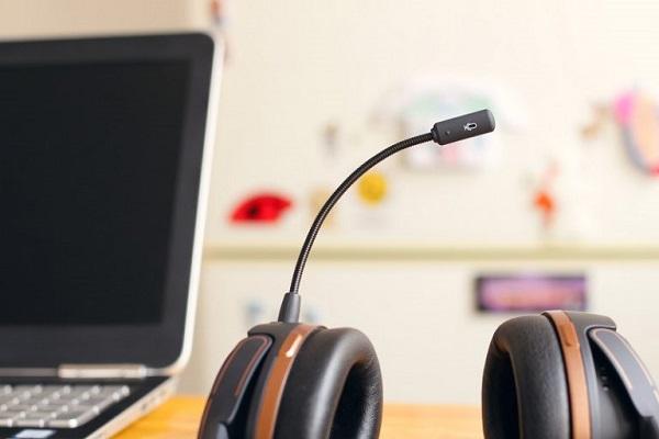 Auf einem Tisch neben einem Computer liegt ein unbenutztes Headset.