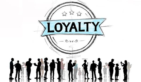 Personen stehen unter einem Schild mit der Aufschrift 'Loyalität'.