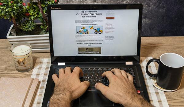 Eine Person schreibt einen Blog-Post auf einem Laptop.