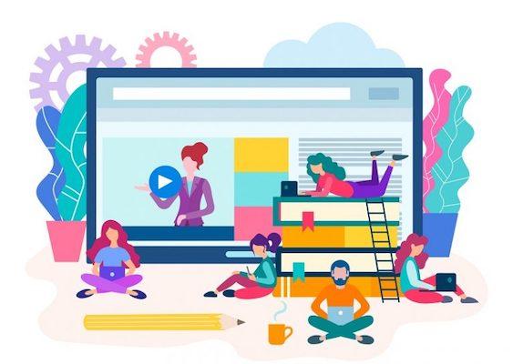 Mitarbeiter, die um einen Laptop sitzen, auf dem ein Video abgespielt wird.