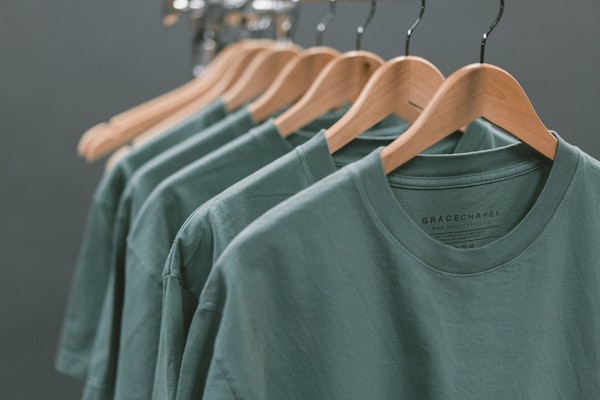 Five identical green T-shirts hanging on a display rack.