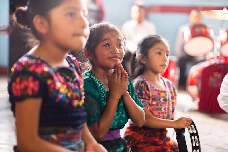 Kinder singen, Mädchen beten.