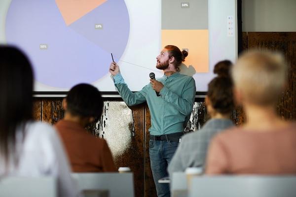 Ein Mann hält in einem Hörsaal eine Präsentation.