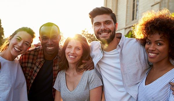 Eine Gruppe von jungen Leuten, die in eine Kamera lächeln.