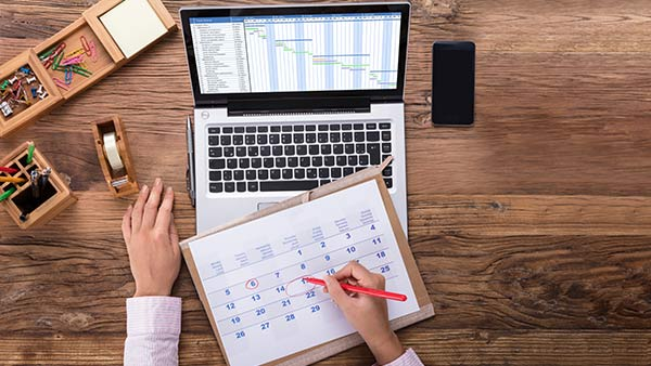 Eine Person erstellt in einem Kalender einen Zeitplan.
