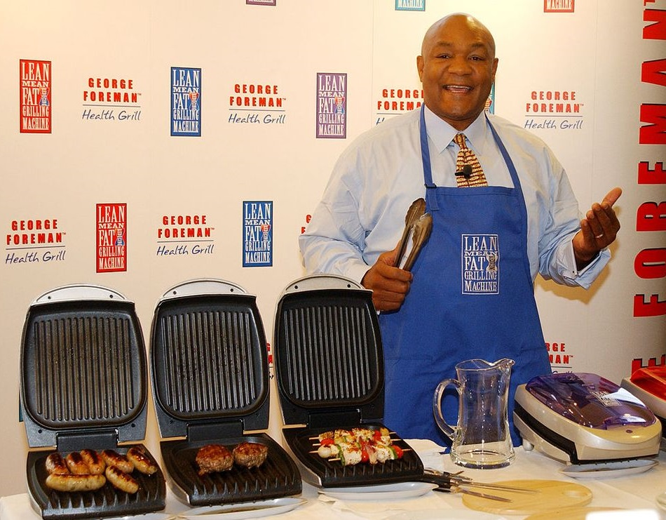 A picture of George Foreman by his signature grill.