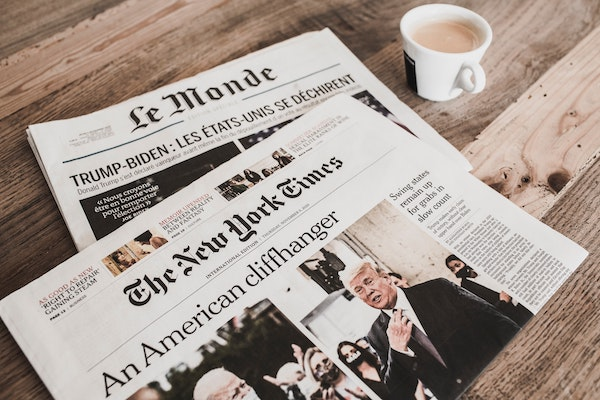 Front pages of New York Times and Le Monde print editions.