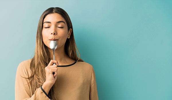 A woman tasting a spoon.