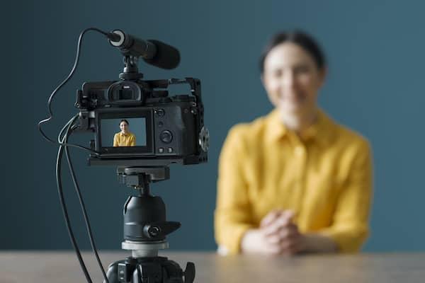 Eine Frau an einem Tisch, die von einer Kamera aufgezeichnet wird.