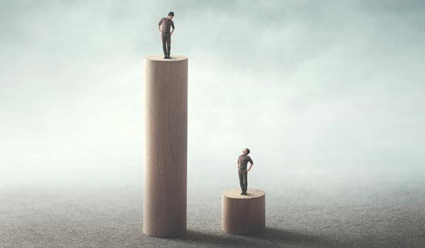 Zwei Personen stehen auf unterschiedlich hohen Podesten.