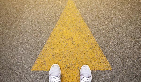 Jemand geht entlang eines Pfeils auf dem Boden.