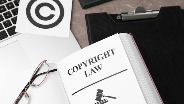 Neben einem Laptop befinden sich ein Urheberrechtssymbol, ein Buch zum Urheberrecht und eine Brille.