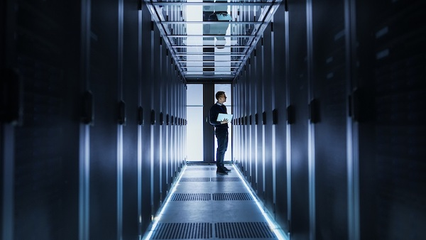 Male IT Engineer Works on a Laptop at the end of a Corridor in a Big Data Center. Rows of Rack Servers