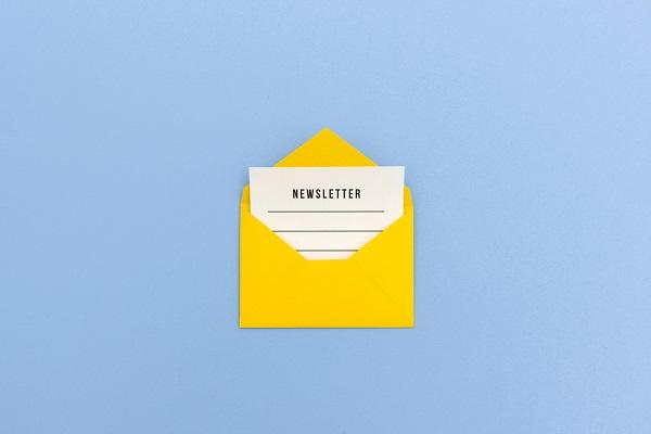 Ein gelber Briefumschlag, aus dem ein Blatt ragt, das mit dem Wort Newsletter überschrieben ist.