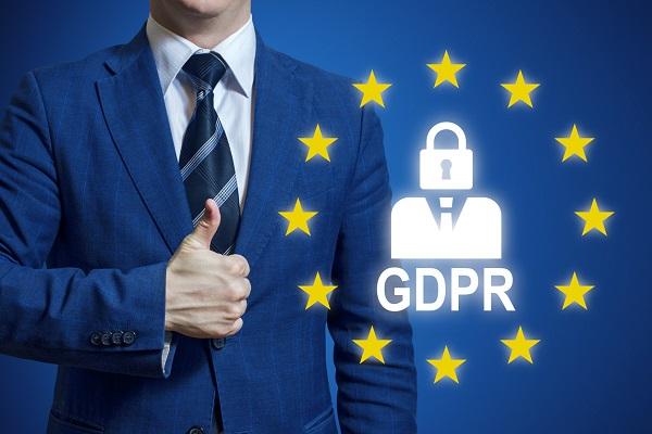 Ein Mann steht neben einem Symbol für die europäische Datenschutzverordnung und gibt seine Zustimmung per Daumen-Hoch-Geste.