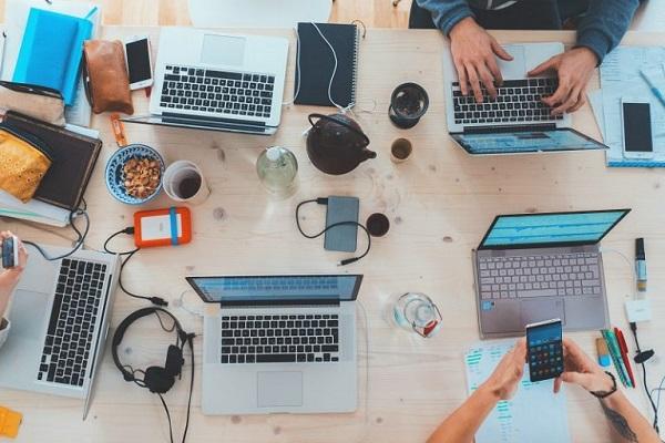 Auf einem Schreibtisch stehen mehrere Laptops, die von Mitarbeitern genutzt werden.