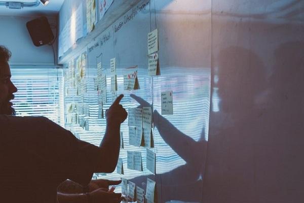 Ein Mann zeigt auf eine Tafel voller Notizen.