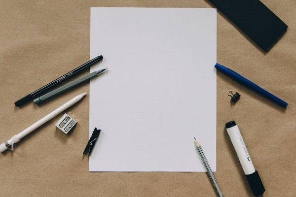 Um ein leeres Blatt Papier herum liegen Schreibutensilien.