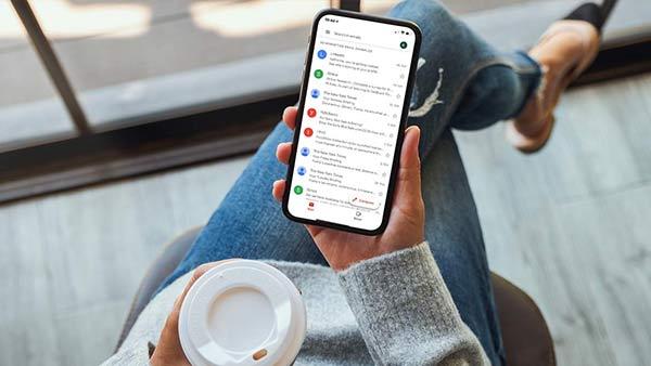 Eine Frau hält ein Smartphone, auf dessen Bildschirm das E-Mail-Postfach angezeigt wird.