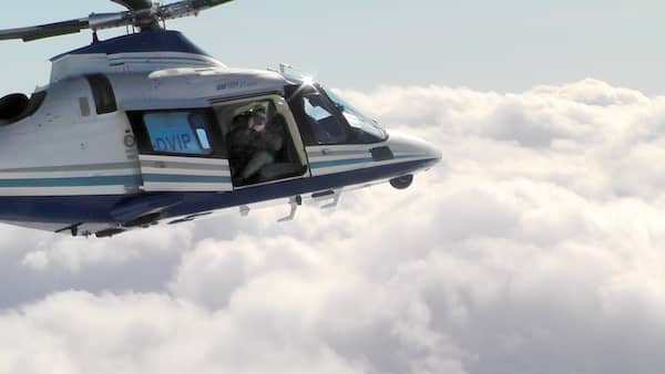 A man films from the open door of a flying helicopter.