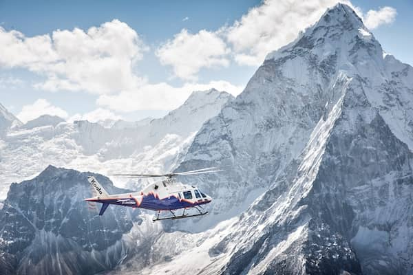 A helicopter flies past a snow-covered mountain range.