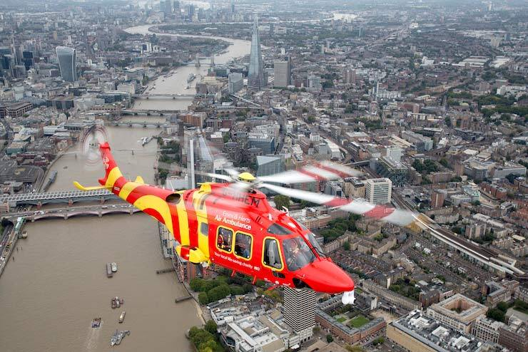A search-and-rescue helicopter flies high above a city.