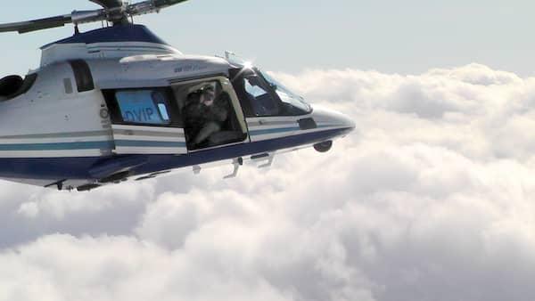 Ein Mann filmt aus der offenen Tür eines fliegenden Hubschraubers.