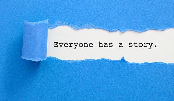 Ein zerrissenes Papier enthüllt den Satz: 'Jeder hat eine Geschichte'.