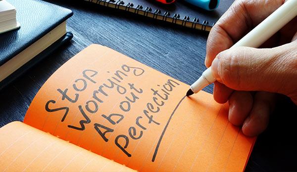 Eine Person schreibt eine Notiz zum Thema Perfektion.