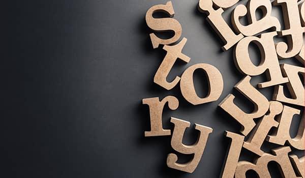 Eine Gruppe von hölzernen Buchstaben bilden das Wort 'Geschichte'.
