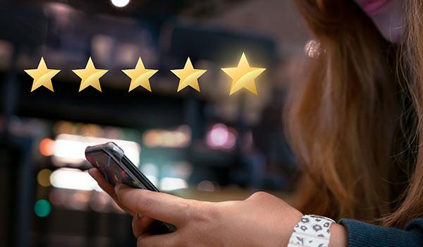 Eine Person hinterlässt über ihr Smartphone eine Bewertung.