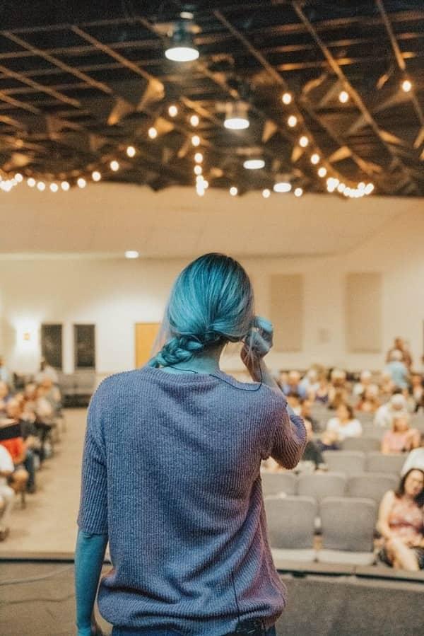 Eine Frau hält einen Vortrag in einem Saal.