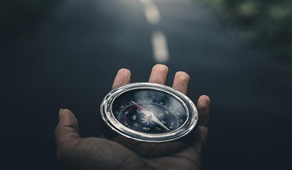 Jemand hält einen Kompass in der Hand.