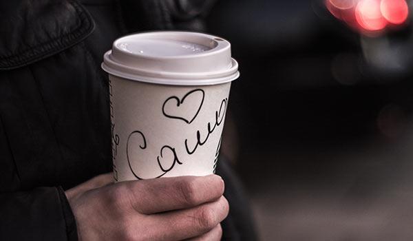 Eine Person mit einem Kaffeebecher, auf dem ihr Name steht.