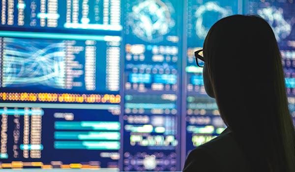 Eine Person analysiert Computer und Daten.