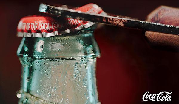 Eine Coca-Cola-Flasche wird geöffnet.