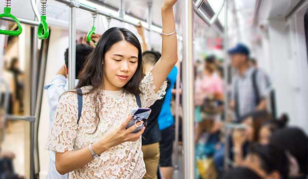 Eine junge Frau steht in einem überfüllten U-Bahn-Waggon und liest etwas auf ihrem Smartphone.