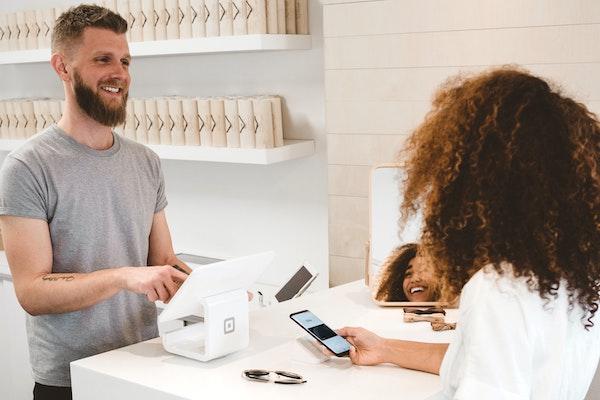 Ein Kleinunternehmer bedient einen Kunden in seinem minimalistisch eingerichteten Laden.