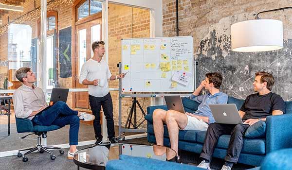 Vier Männer in einem trendigen Startup-Büro diskutieren über die Markenidentität.