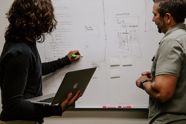 A man and woman plan an email strategy on a whiteboard.