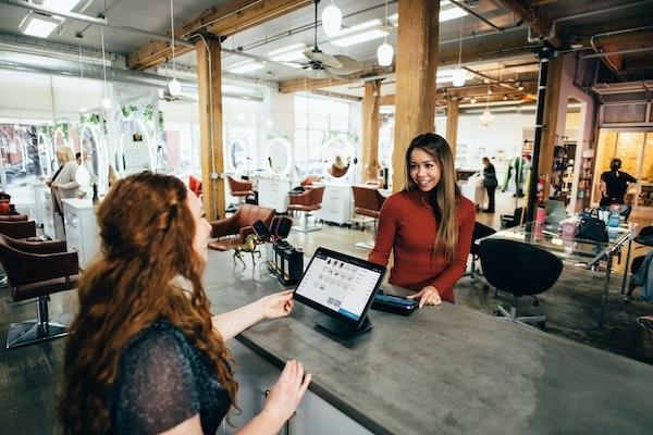 Eine Frau in einem trendigen, industriellen Laden rechnet eine Kundin ab.