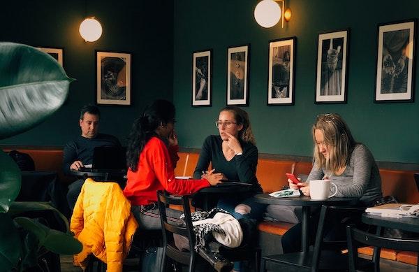 Kunden sitzen in einem modernen Café, hinter ihnen hängen Schwarz-Weiß-Fotos an der Wand.