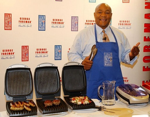 Ein Bild von George Foreman neben seinem Markenzeichen, dem Grill.