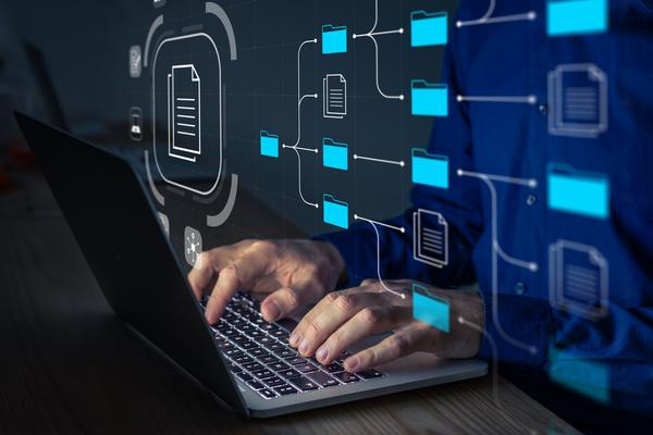 Darstellung eines Mannes, der am Laptop organisierte Dateien durchsucht.