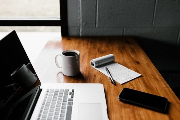 Ein Laptop und ein Mobilgerät auf einem Schreibtisch.