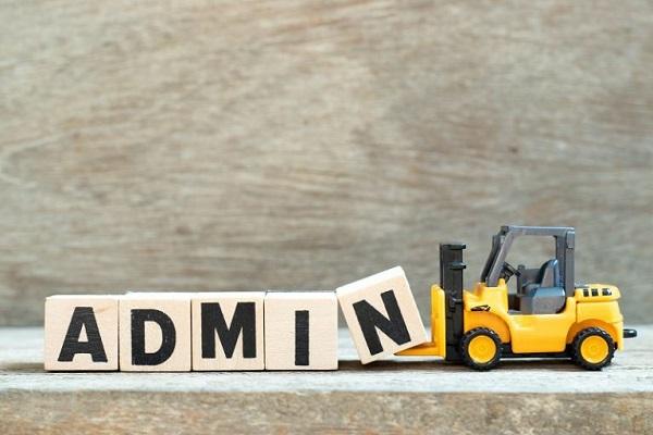 Ein Spielzeuggabelstapler schiebt das Wort 'Admin' aus Holzklötzen gebildet vor sich her.