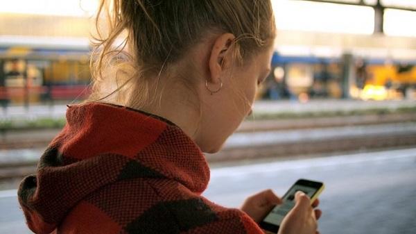 Eine junge Frau nutzt ein Mobilgerät im Freien.