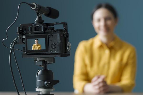 Eine Kamera zeichnet ein Video von Frau vor einem dunklen Hintergrund auf.