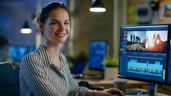 Eine Mitarbeiterin an einem Computer beim Schneiden eines Videos.