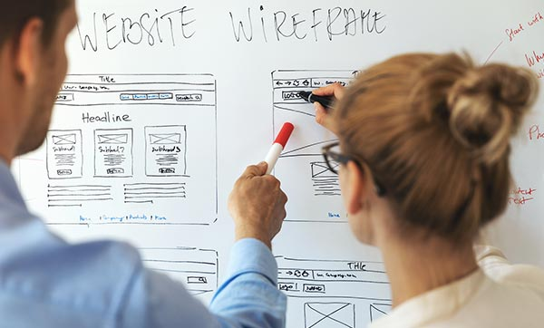 Web designers sketch out wireframe on a whiteboard.